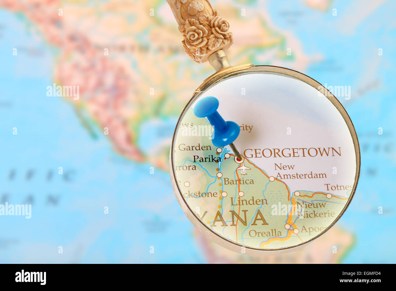 Blue tack on map with magnifying glass looking in on Georgetown, Guyana - Stock Image