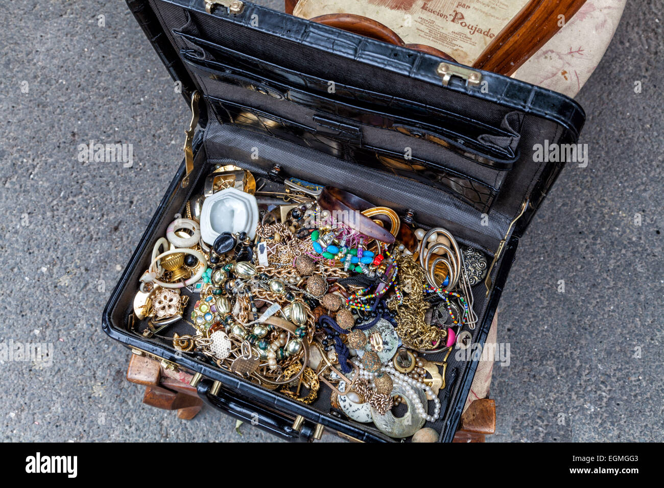 A suitcase full of treasure! Junk jewelery fills a suitcase at the street market. - Stock Image