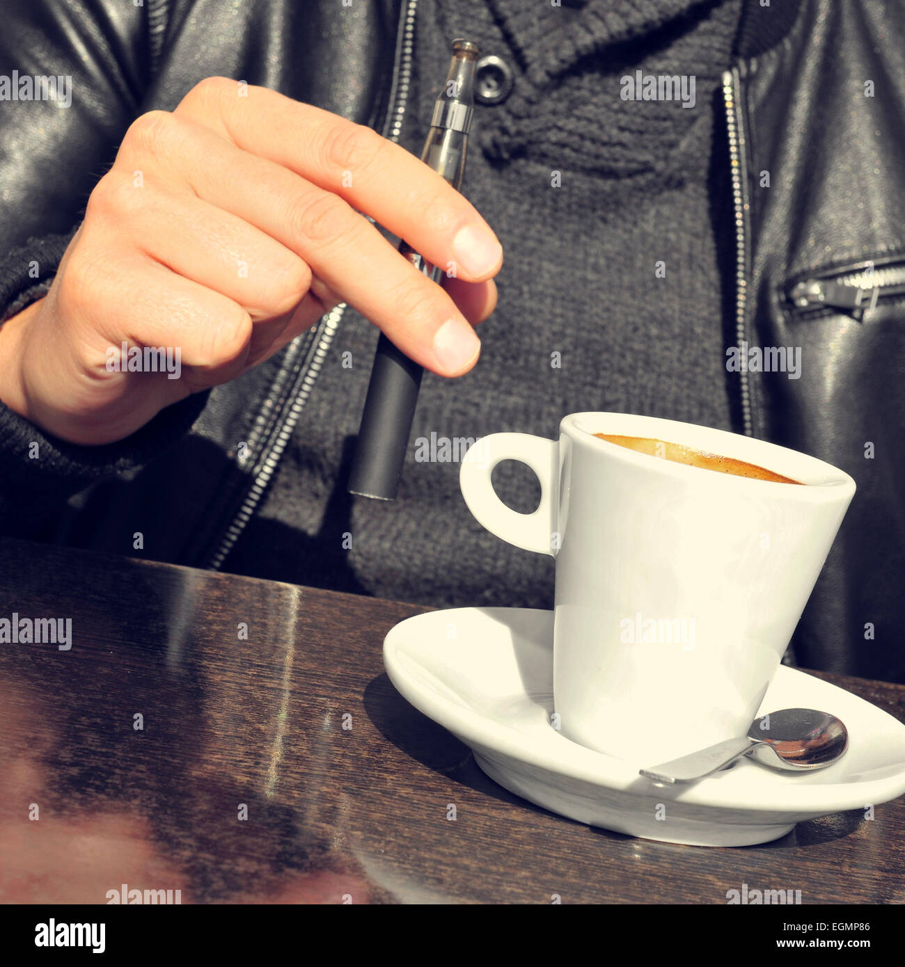 closeup of a young man with an electronic cigarette and a cup of coffee in the terrace of a cafe - Stock Image