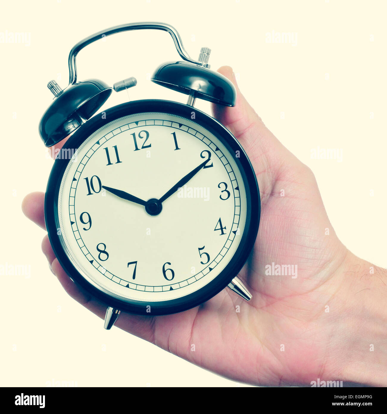 a man holding a mechanical alarm clock in his hand, with a retro effect - Stock Image