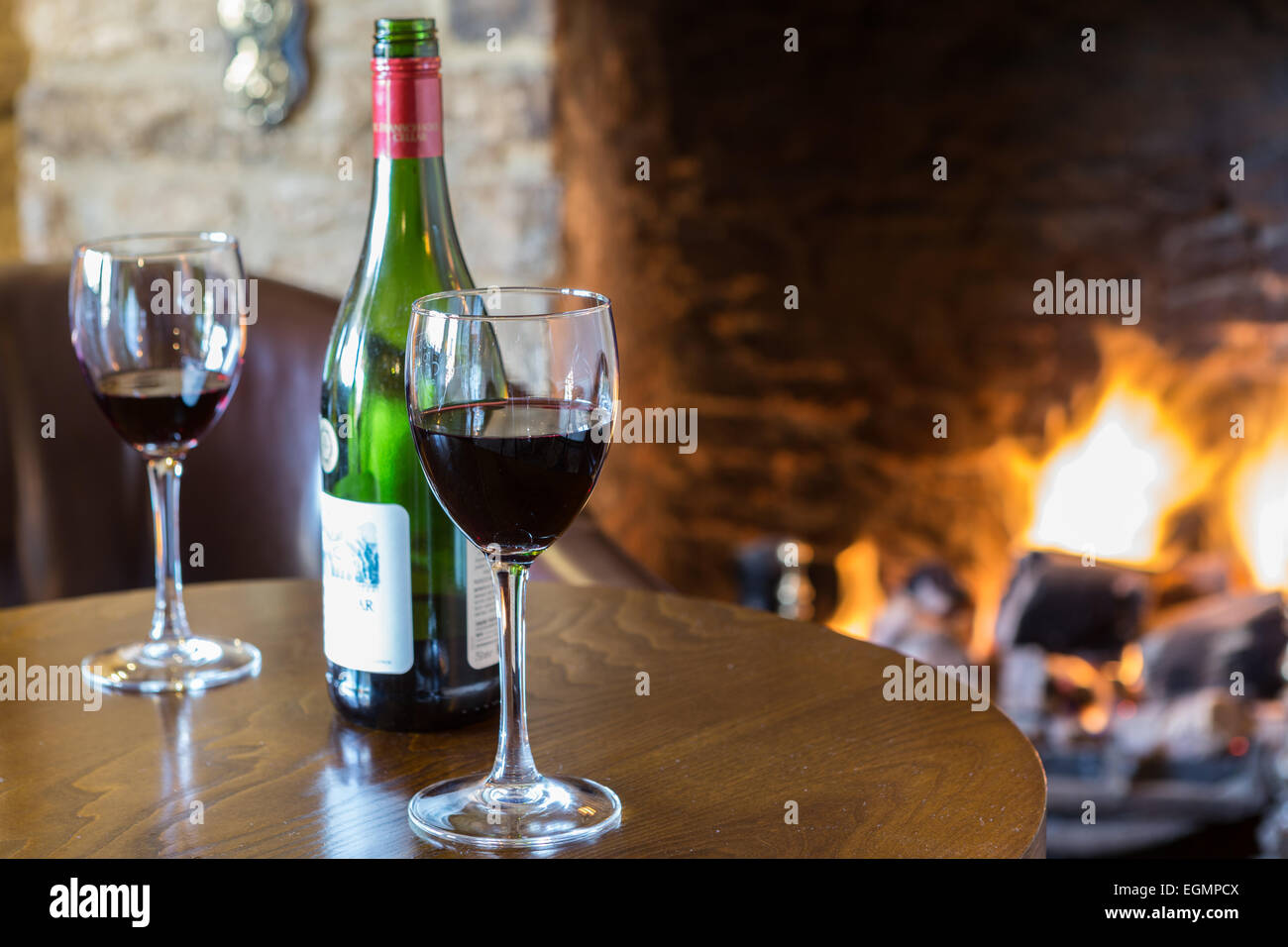 Bottle of red wine with two glasses in cosy pub - Stock Image