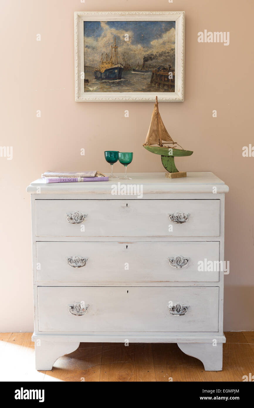 Simple wooden chest of drawers with vintage items - Stock Image