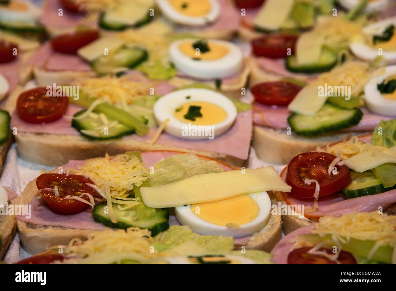Sandwiches with egg, cheese, cucumber, ham and cherry tomatoes. Food and drink theme. Stock Photo