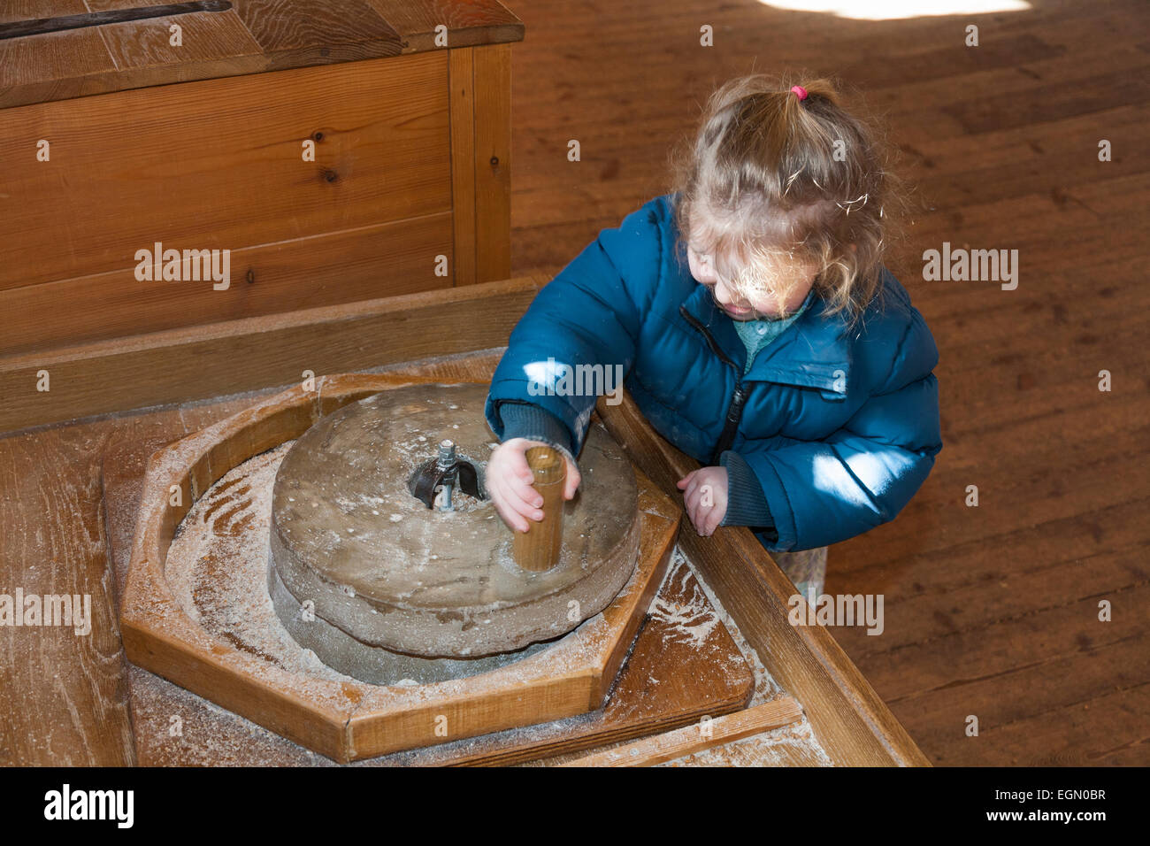 Child Kid Using Grain Grinding Wheel Stone Grindstone Display Inside Interior Winchester Mill On River Itchen UK