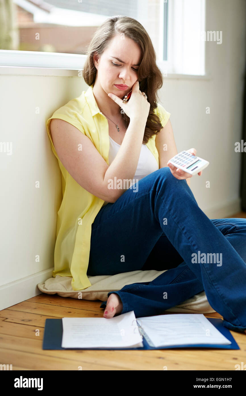 Woman working out finances sat on floor - Stock Image