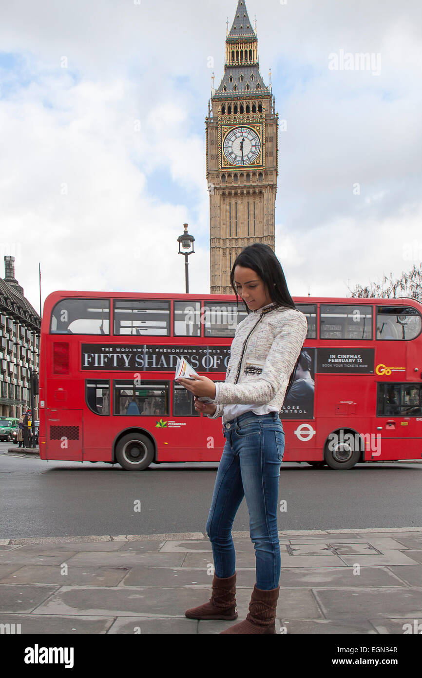 An attractive young woman reading a guide book in London - Stock Image