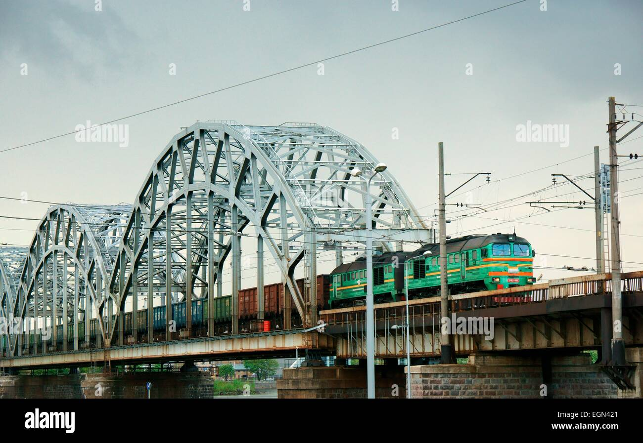 Riga, Latvia. Latvian freight ore train entering Riga central station across the Daugava River rail bridge - Stock Image