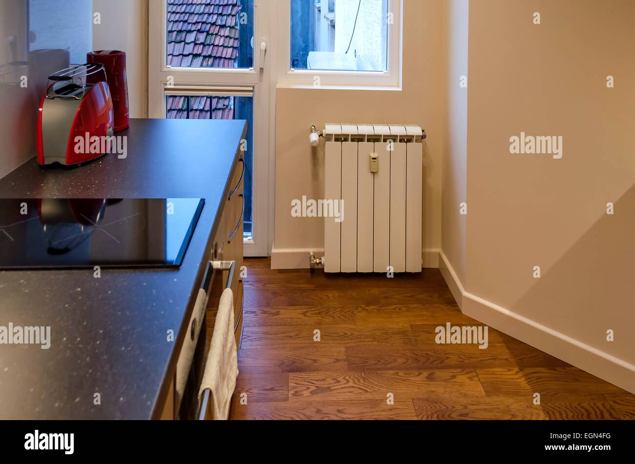 Part of kitchen and heating radiator - Stock Image
