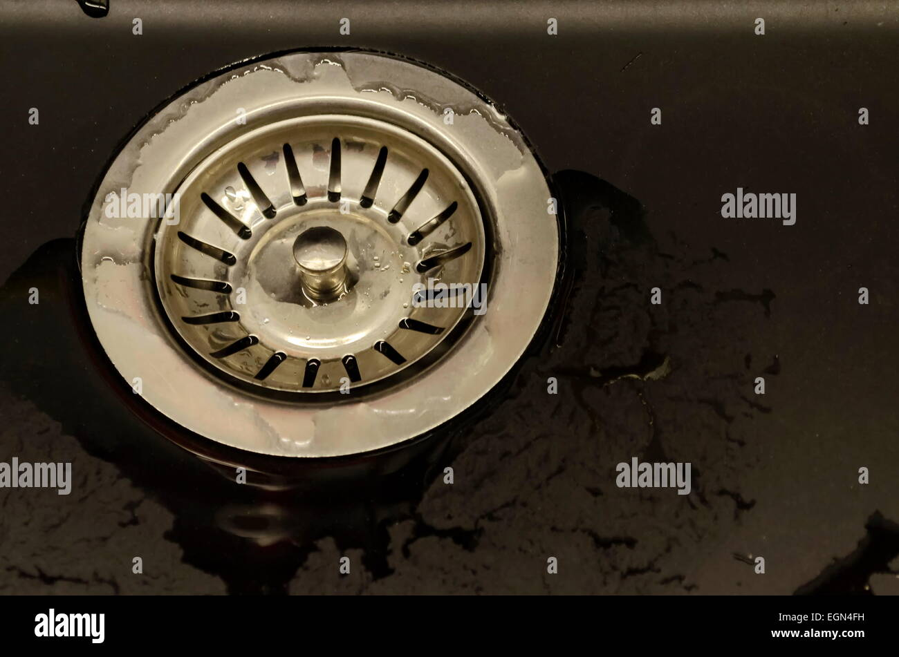 Metal sifter at kitchen sink - Stock Image