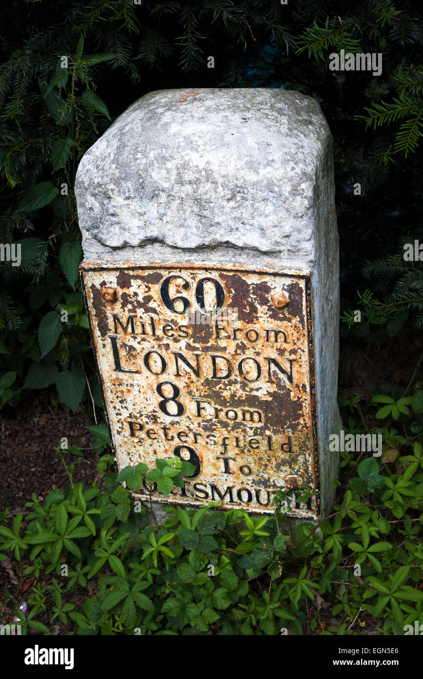 Old worn traditional milestone marker with metal plate stating 60 miles from London Stock Photo