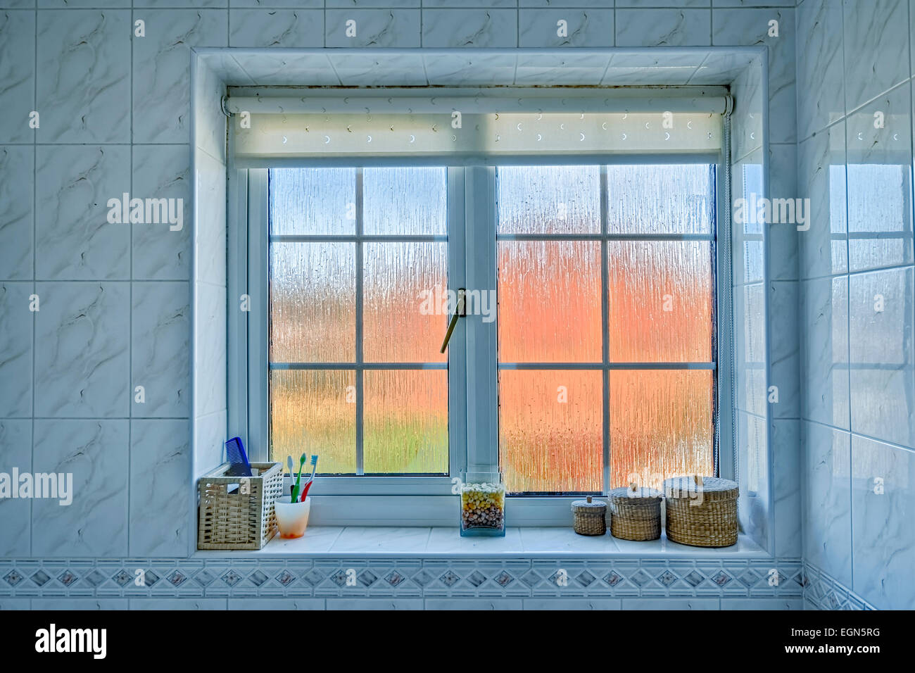 Frosted Glass Bathroom Window With Distorted Orange/blue Exterior, And  Various Items On The Windowsill.