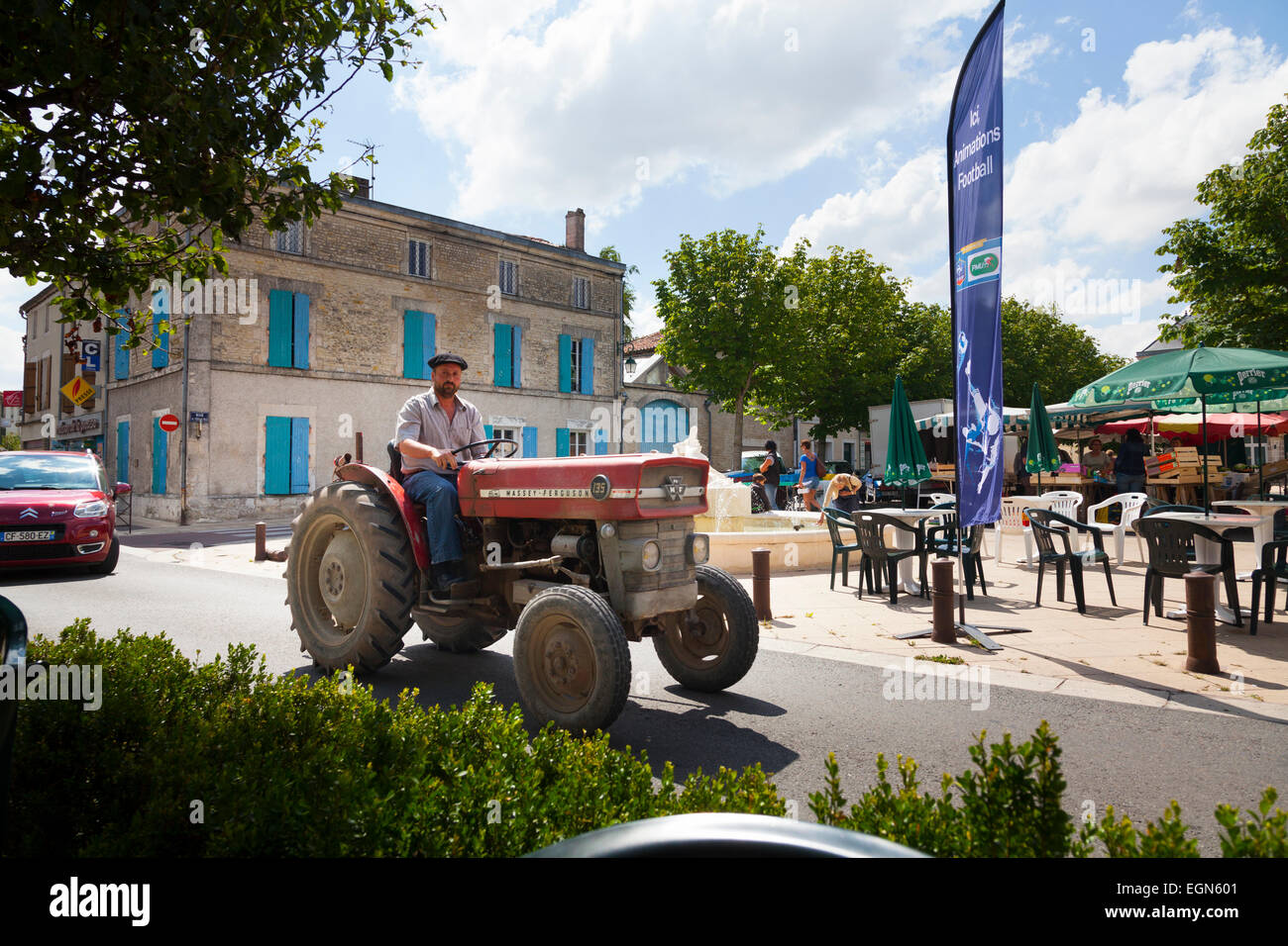 Frenchman in beret driving tractor through French village centre - Stock Image