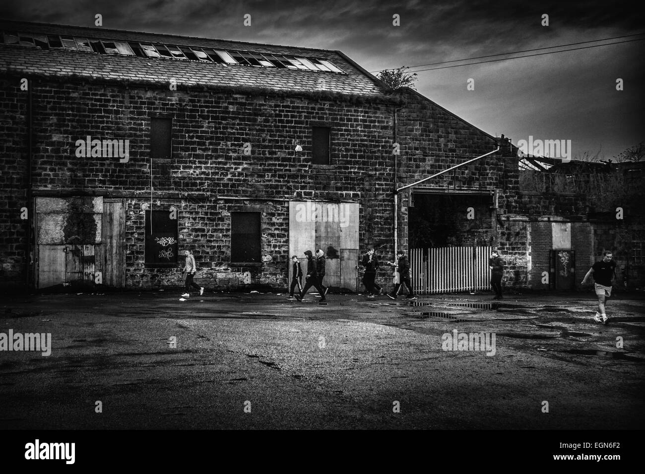 Derelict Yorkshire stone mill/warehouse with youths - Stock Image
