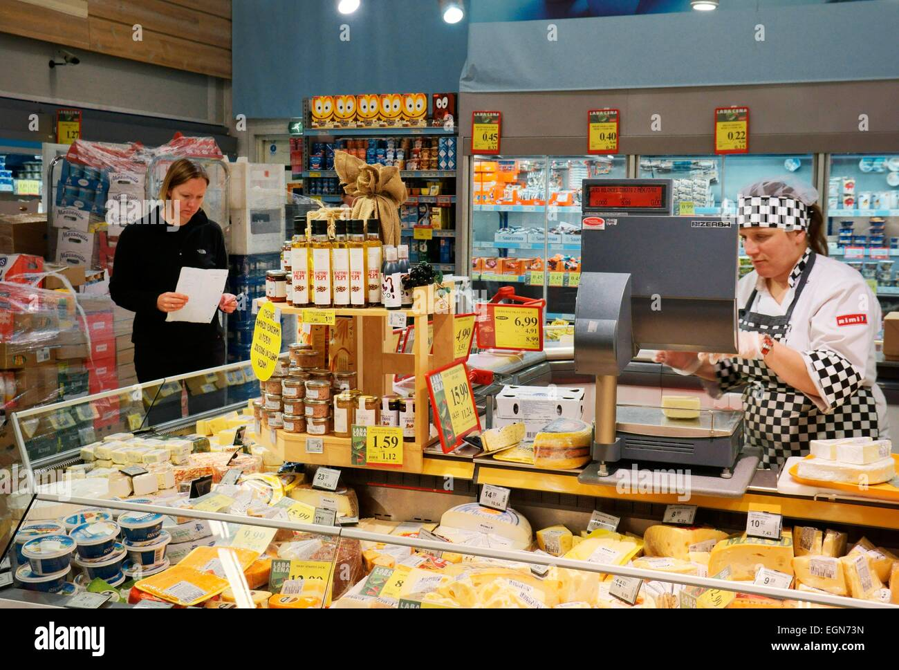 Riga Latvia. Interior of Rimi hypermarket Latvian store. Assistant and customer at cheese dairy deli counter with - Stock Image
