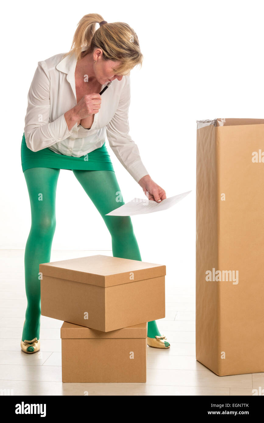 Woman working in office checking boxed deliveries Stock
