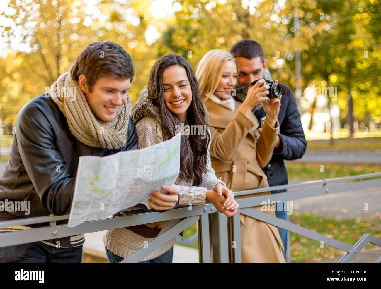 group of friends with map and camera outdoors - Stock Image
