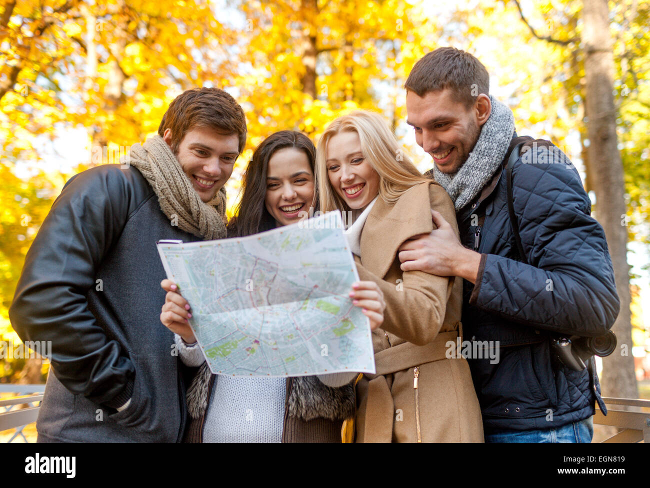 group of friends with map outdoors - Stock Image