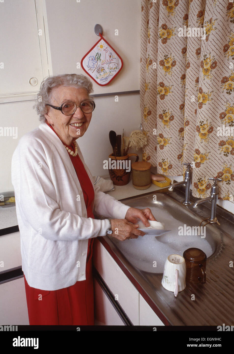 Old lady washing up at the sink in the kitchen - Stock Image