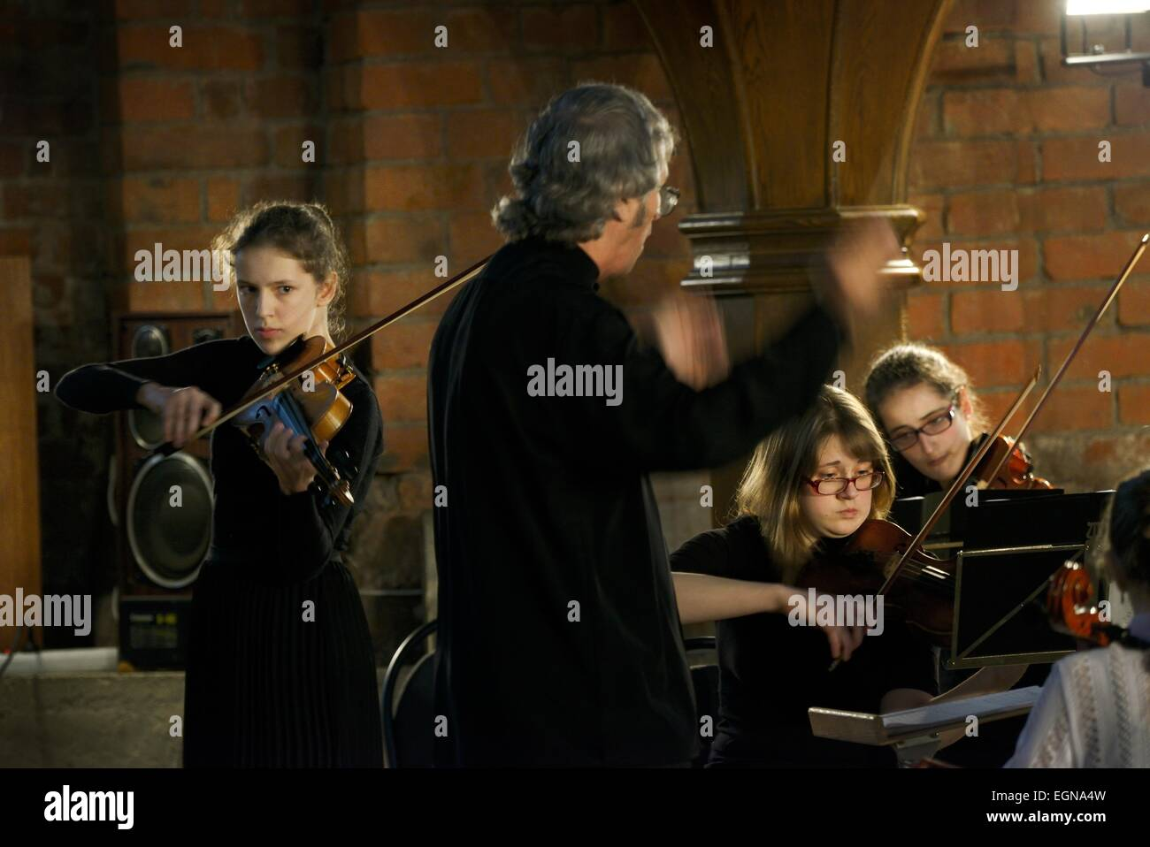 Riga Latvia. Conductor, lead violinist and members of youth orchestra during classical music recital inside Saint - Stock Image