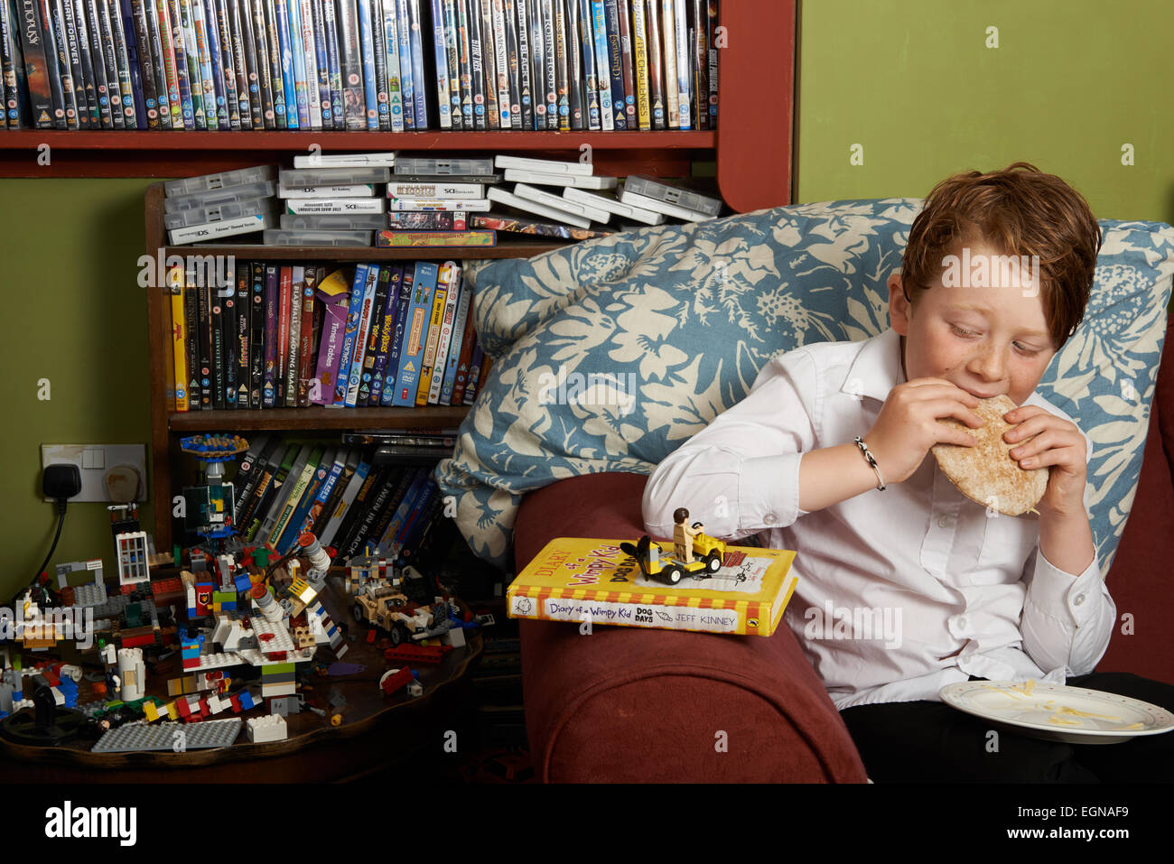 10-year old boy at home after school eating a pitta bread sandwich - Stock Image