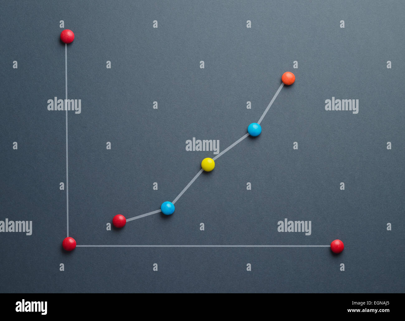 Growth graph concept made of colorful button shaped candies over dark blue background. This image is a photograph - Stock Image