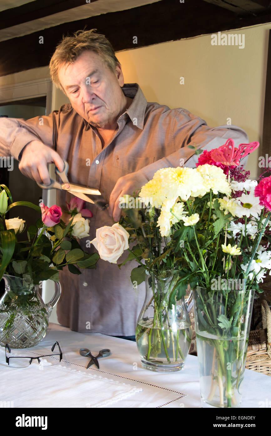 Senior man arranging cut flowers in vases - Stock Image