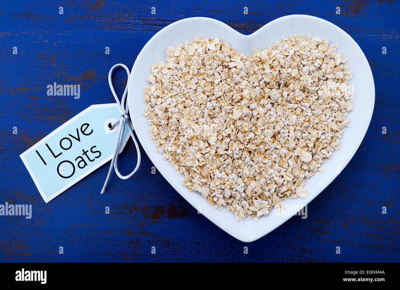 Plate of nutritious and healthy oat flakes in heart shaped bowl on dark blue rustic wood table, with I Love Oats Stock Photo
