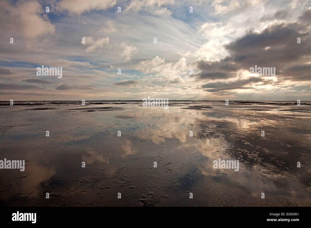 dark clouds reflected in the shallow water of the north sea, national park Wadden Sea,  Westerhever, Schleswig-Holstein, - Stock Image