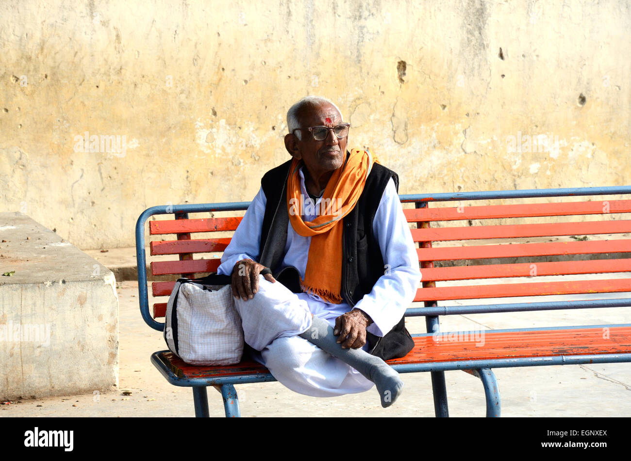 An Indian  wedding mantra chanter sitting on a bench at a railway station Madhya Pradesh India - Stock Image