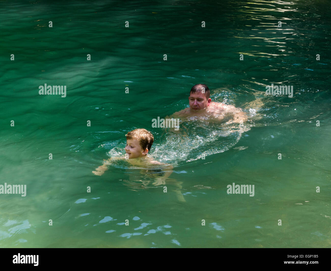 Father and son tourists cooling off in clean inviting river Rio Bajabonico  Puerto Plata Dominican Republic on a - Stock Image