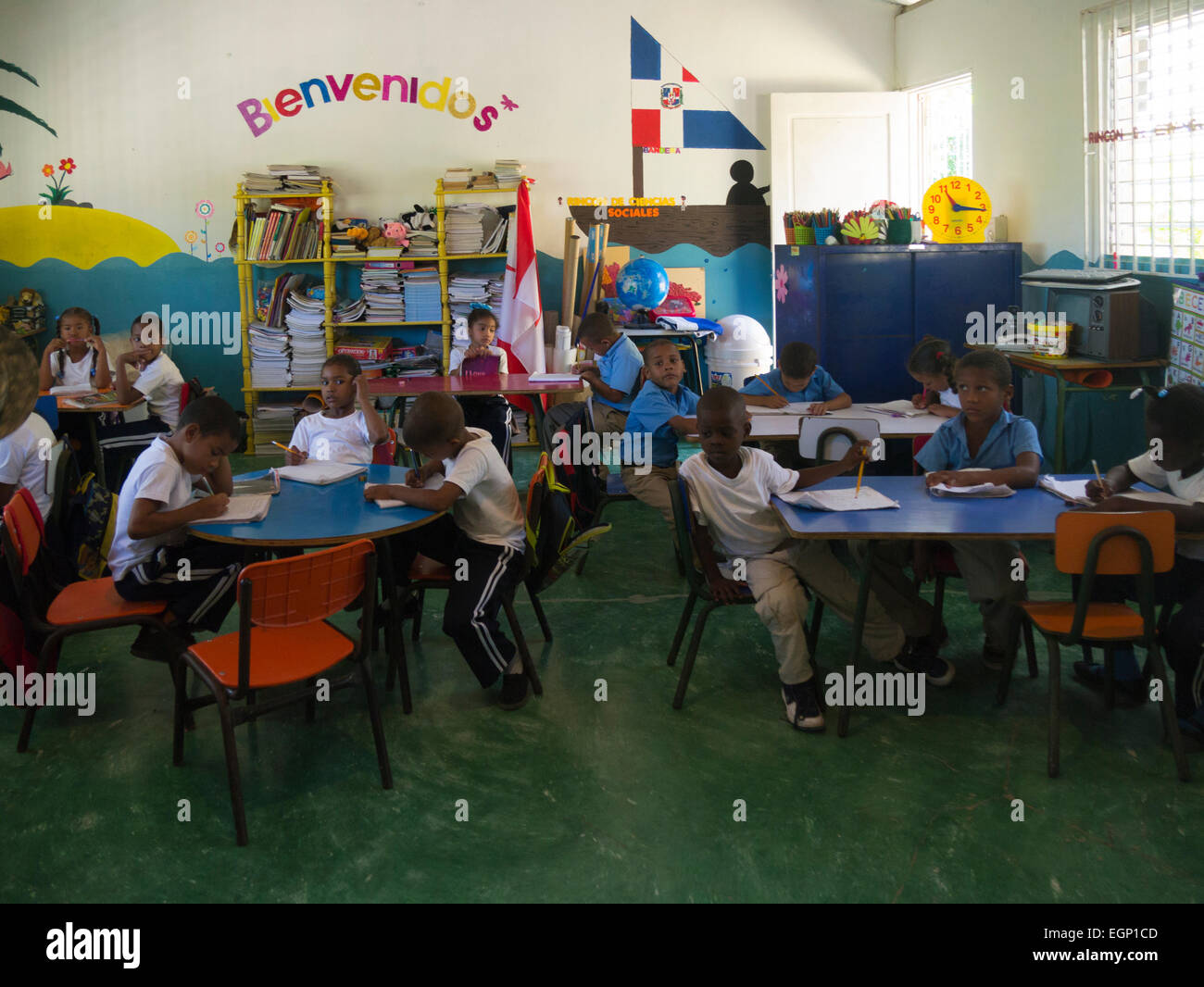 Primary school children in class Puerto Plata Dominican Republic concentrating on their lessons despite a visit - Stock Image