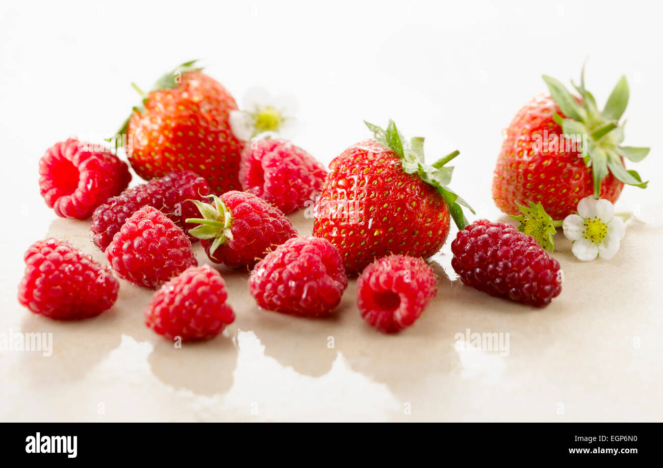 Raspberry, Rubus idaeus cultivar and Strawberry, Fragaria cultivar. Several berries with calyxes and strawberry Stock Photo