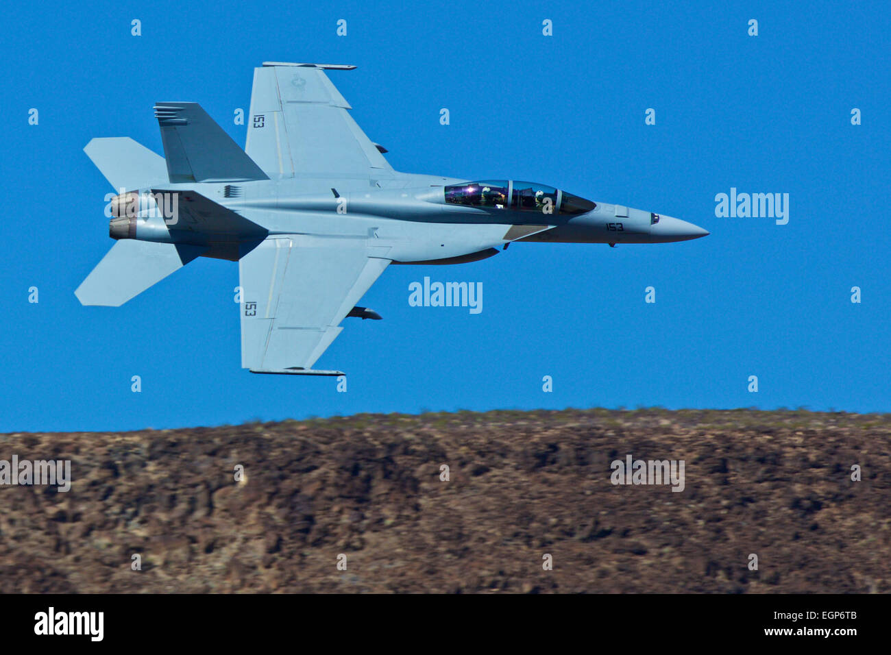 Close Up Topside View Of A US Navy F/A-18F Super Hornet Jet Fighter Flying Along The Rim Of Rainbow Canyon, California. Stock Photo
