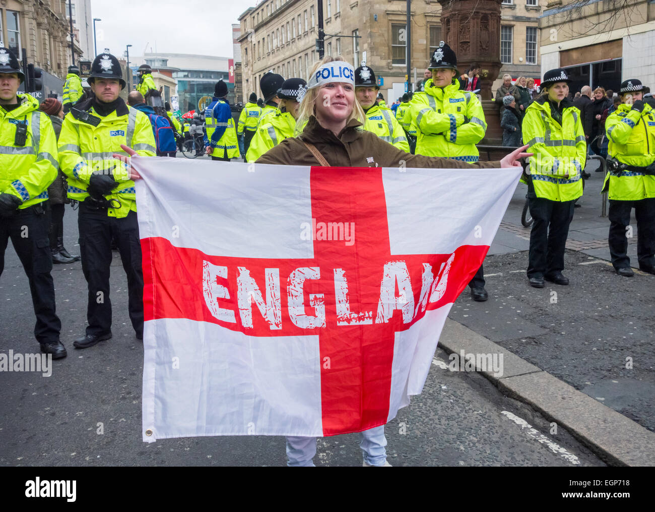 A woman holds an England flag in front of a police line at Pegida protest in Newcastle upon Tyne, England. UK - Stock Image