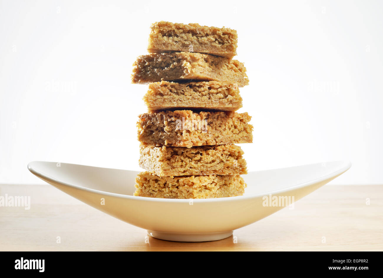 Gluten free home made flapjack served on a curved dish - Stock Image