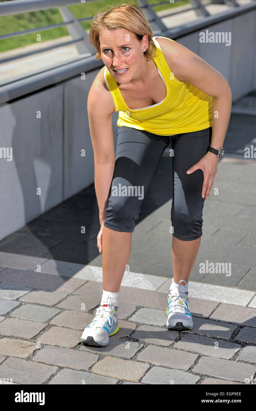 Jogging woman having a cramp in the calf - Stock Image