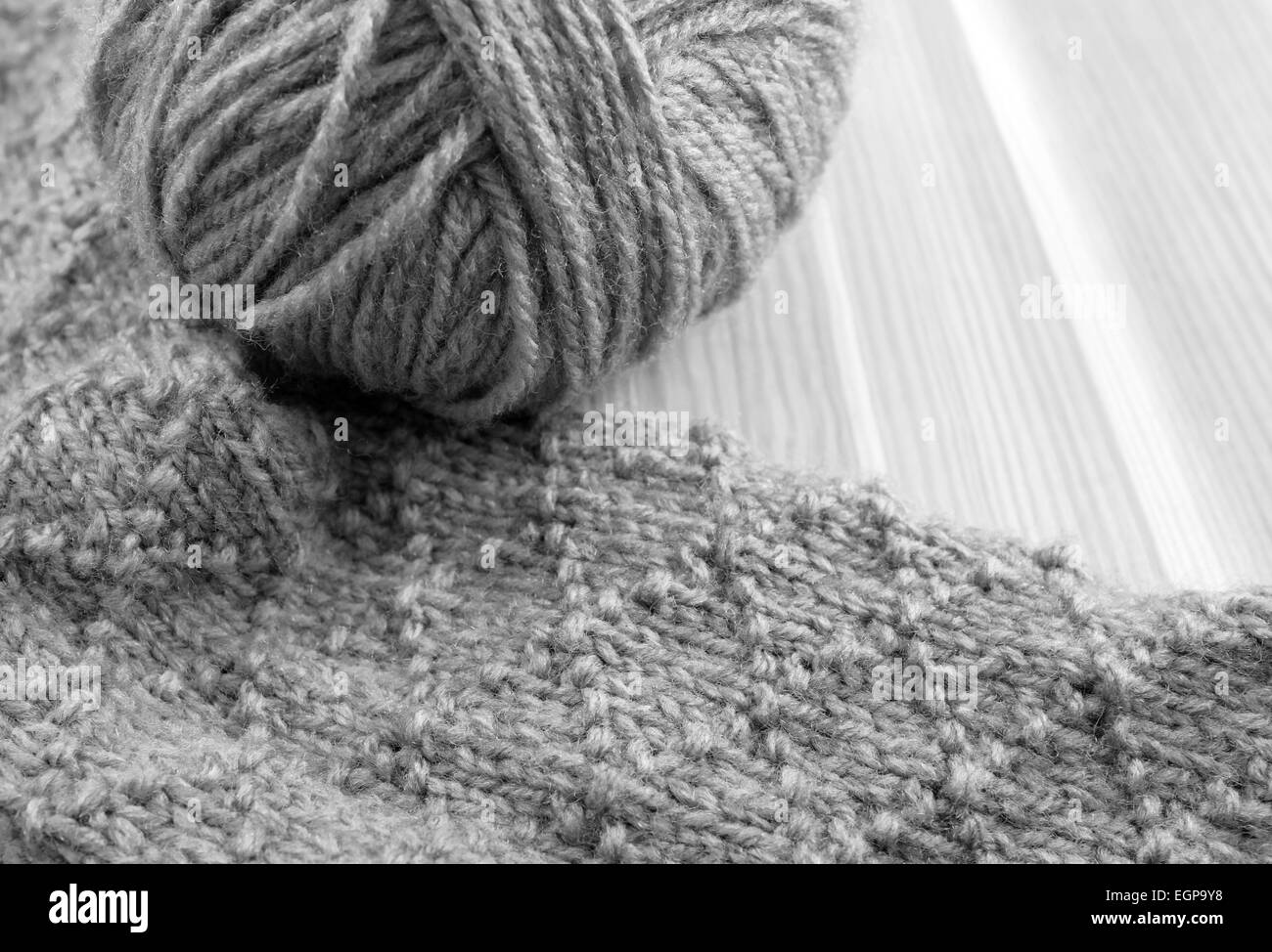 Patterned knitting with ball of wool, on wooden table - monochrome processing - Stock Image