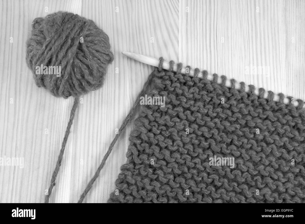 Ball of wool and garter stitch on a knitting needle - monochrome processing - Stock Image