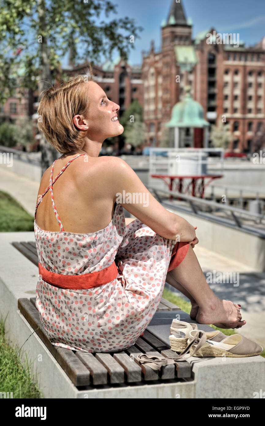 Woman sitting on a bench enjoying the sun - Stock Image
