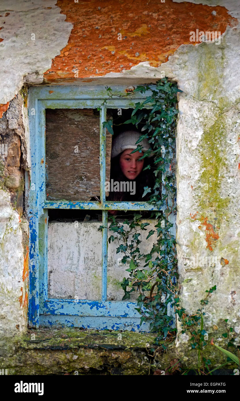 Young girl peeping  mysteriously out of the dirty broken window in an old abandoned house in Co. Cork Ireland Stock Photo