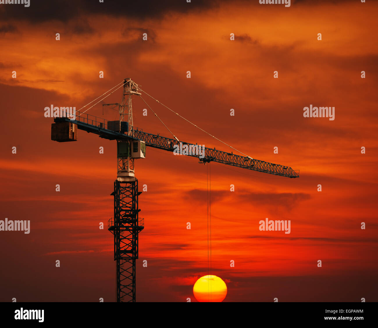 Trick shot appears to show the sun suspended from the cables of a construction crane with a red sky in the background. - Stock Image