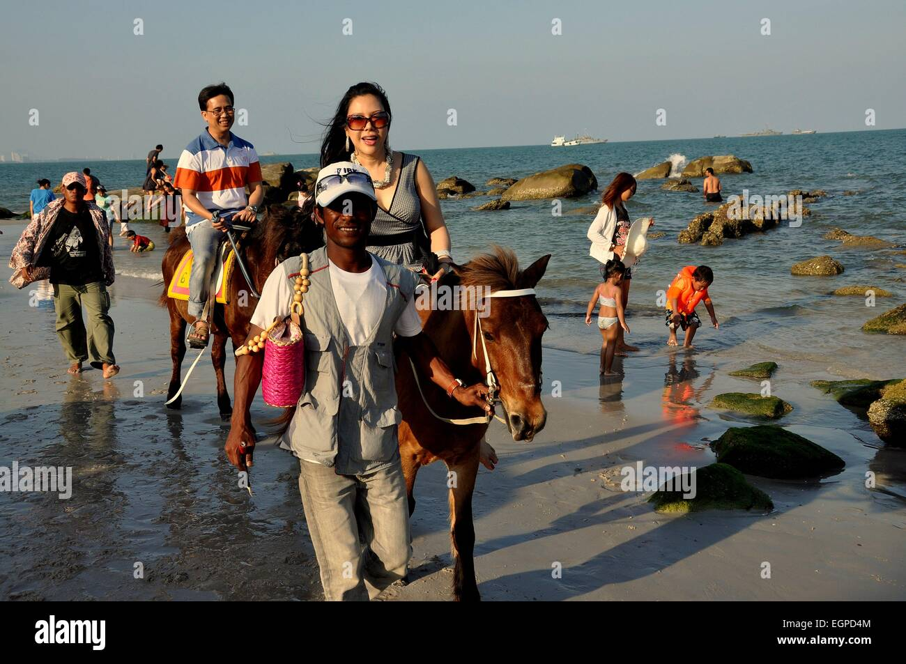 Hua Hin, Thailand: Handler escorts two Asian tourists riding rented horses  along the edge