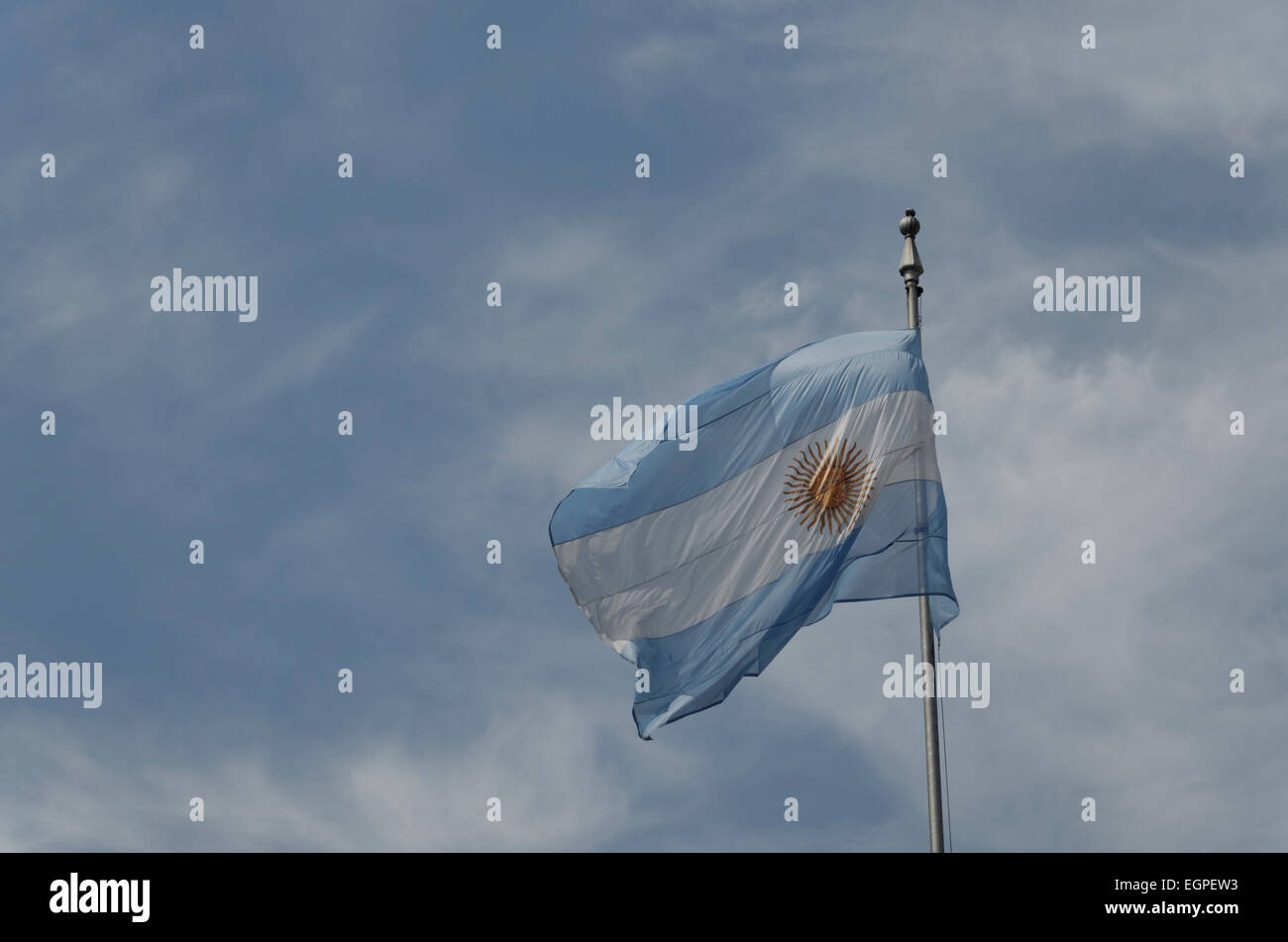 The flag of Argentina flying flapping in the wind on a flagpole against a blue sky - Stock Image