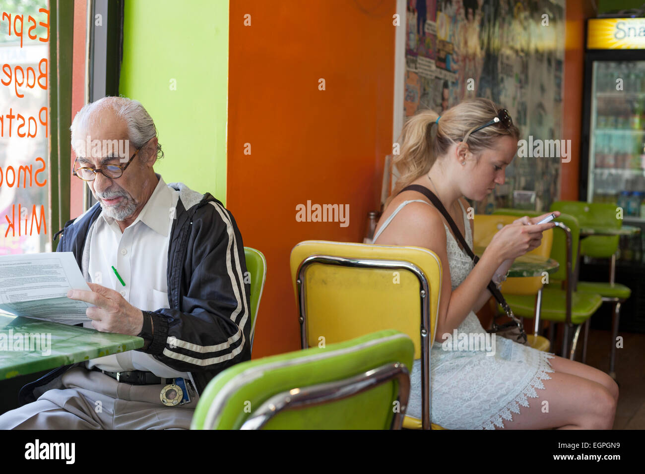 A man and woman sit in a restaurant immersed in their own activities. - Stock Image