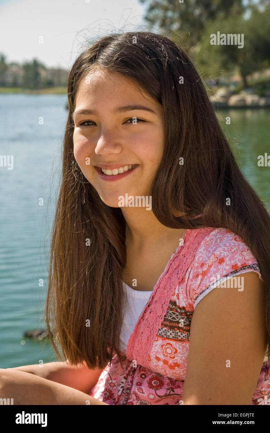 Hispanic-Caucasian teen girl 11-13 year old smiling portrait in park with lake.mixed race, racial mix diversity - Stock Image