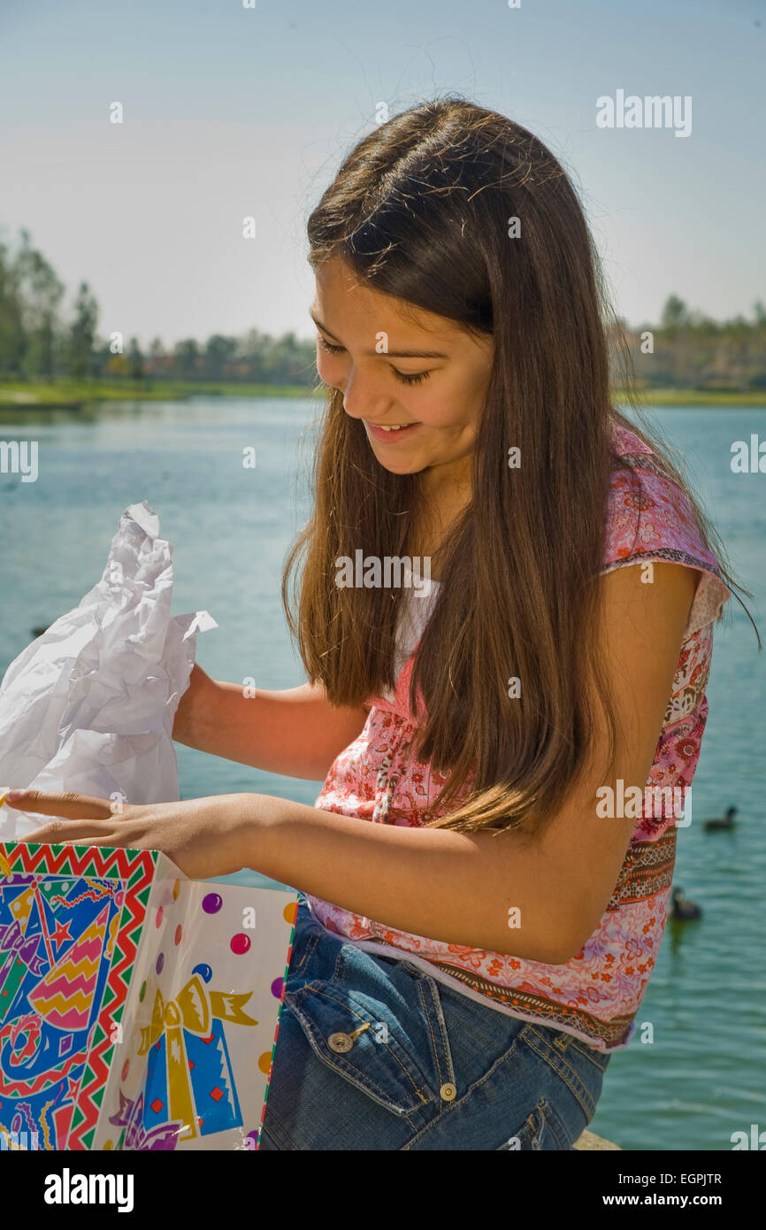 Young Person People Tween Tweens Hispanic Caucasian Girl 11 13 Year Old Child Children Opens Opening Birthday Present Gift Outdoors MR C Myrleen Pearson