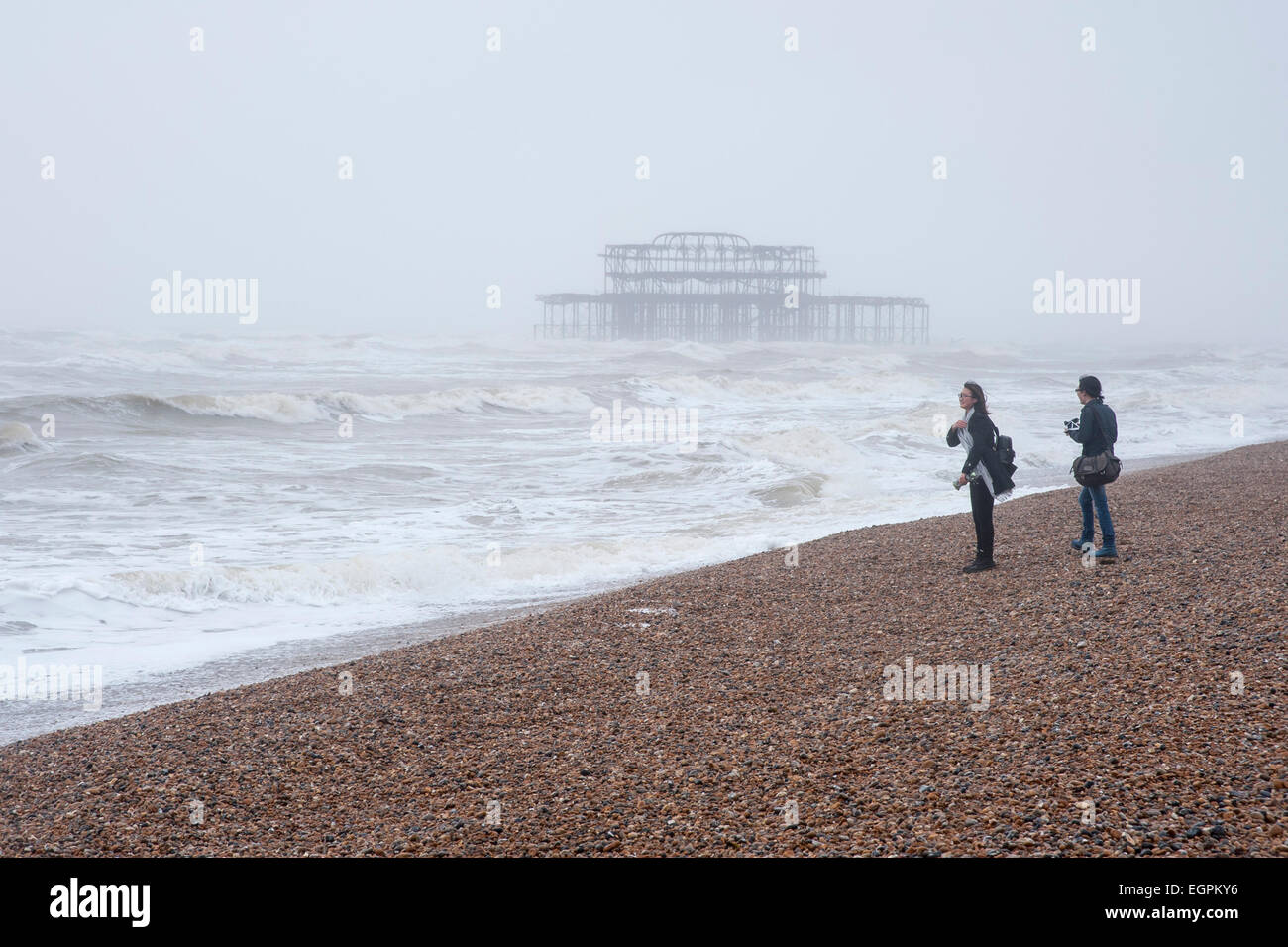Brighton, Sussex, UK, 28 February 2015.  A pair of tourists brave the elements on the pebble beach as heavy rain - Stock Image