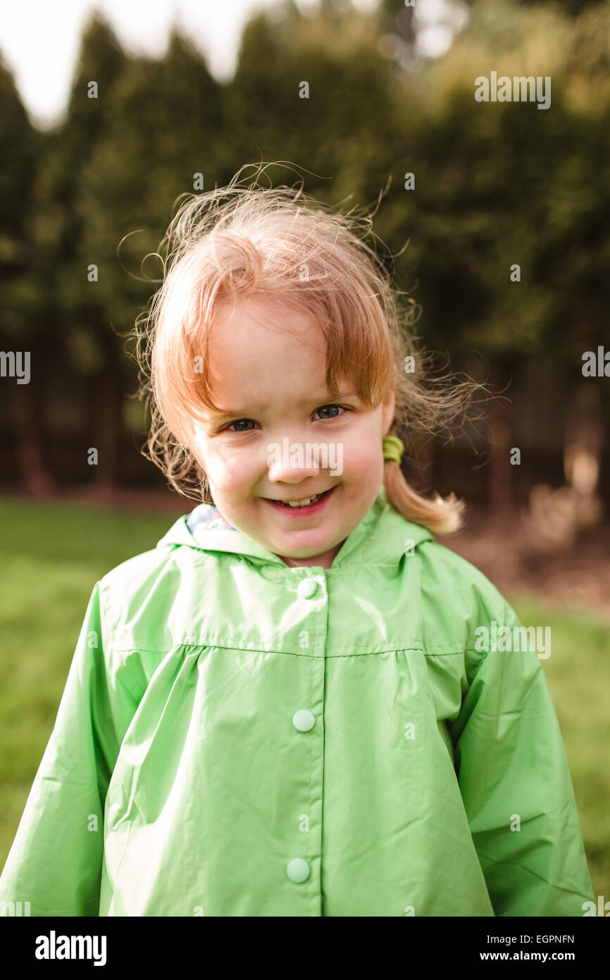 Portrait of a young girl at a park with a rain coat on. This lifestyle photo was shot with natural light. - Stock Image