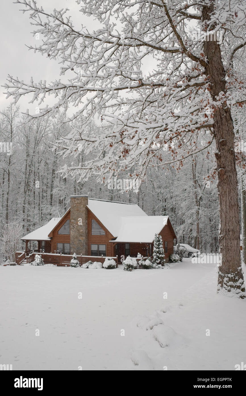 Snow covered log home in North Carolina. Surrounded by trees. - Stock Image
