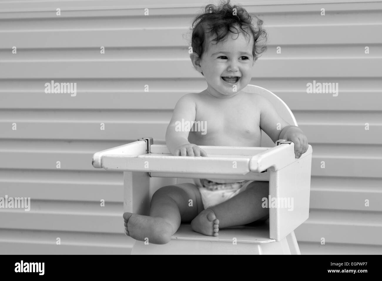 Smiley baby girl (age 8 months) sit on high chair.(BW) - Stock Image